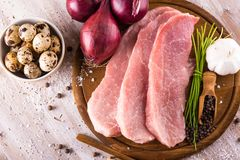 Top view on raw pork meat with few spices and eggs. Horizontal photo with few slices of raw pork meat on wooden plate with spice as pepper or paprika around Stock Photography