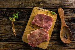 Top view raw pork  two pieces have  spices and pepper. Oil and salt on old wooden table. Royalty Free Stock Images