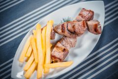 Top view of a ready-made shish kebab and French fries on a white plate. Plate on the table with a blue tablecloth in royalty free stock photo