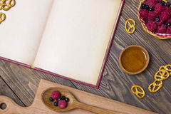 Top view of a recipe book with ingredients on a wooden table nex Royalty Free Stock Image
