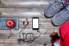 Healthy eating and equipment for leisure and outdoor sports, on rustic wooden background. Top view of a red apple, sport shoes, audio earphones, smartphone, hat Royalty Free Stock Photos
