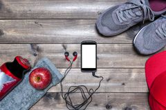 Healthy eating and equipment for leisure and outdoor sports, on rustic wooden background. Top view of a red apple, sport shoes, audio earphones, smartphone, hat Stock Image