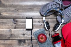Healthy eating and equipment for leisure and outdoor sports, on rustic wooden background. Top view of a red apple, sport shoes, audio headphone, smartphone, hat Stock Images