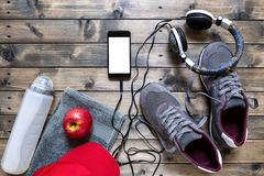 Healthy eating and equipment for leisure and outdoor sports, on rustic wooden background. Top view of a red apple, sport shoes, audio headphone, smartphone, hat Stock Photography