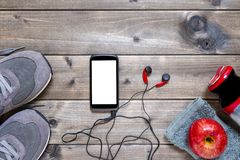 Healthy eating and equipment for leisure and outdoor sports, on rustic wooden background. Top view of a red apple, sport shoes, audio headphone, smartphone Stock Photography