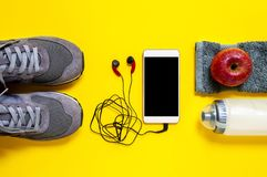Healthy eating and equipment for leisure and outdoor sports, on yellow background. Top view of a red apple, sport shoes, audio headphone, smartphone, towel and Stock Photo