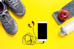 Healthy eating and equipment for leisure and outdoor sports, on yellow background. Top view of a red apple, sport shoes, audio headphone, smartphone, towel and Stock Photography