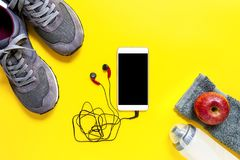 Healthy eating and equipment for leisure and outdoor sports, on yellow background. Top view of a red apple, sport shoes, audio headphone, smartphone, towel and Stock Photos