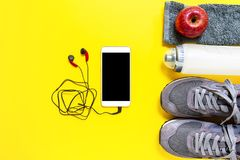 Healthy eating and equipment for leisure and outdoor sports, on yellow background. Top view of a red apple, sport shoes, audio headphone, smartphone, towel and Royalty Free Stock Photo
