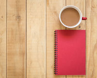 Top view of red book and coffee cup on wooden table. Background Stock Photography