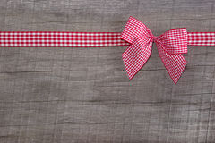 Top view of a red checked ribbon decoration on wooden background Royalty Free Stock Photo