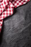Top of view red checkered tablecloth on black slate board.  stock photography