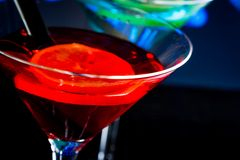 Top of view of red cocktail with blue light disco background with space for text Stock Photos