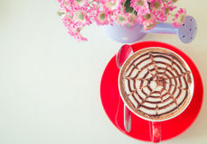 Top view red cup of coffee with vase of flower. On vintage background Royalty Free Stock Photo
