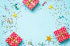 Top view of a red dotted gift boxes, golden magic wands, colorful confetti and ribbons over blue background. Celebration concept. Royalty Free Stock Photo