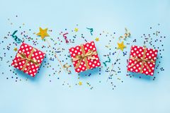 Top view of a red dotted gift boxes, golden magic wands, colorful confetti and ribbons over blue background. Celebration concept. Royalty Free Stock Image