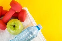 Top view of red dumbbells, green apple and fresh water bottle with dew on white towel and yellow space Royalty Free Stock Photos
