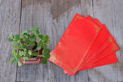 Top view of red envelope packet or ang paw and Euphorbia milli on old wooden background. Chinese new year festival concept Royalty Free Stock Photo