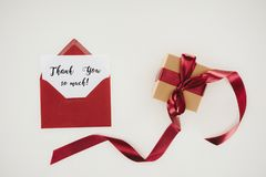 Top view of red envelope with thank you so much lettering on paper and gift box. Isolated on white Stock Image