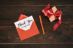 Top view of red envelope with thank you so very much lettering on paper and gift box. On wooden table Royalty Free Stock Photography