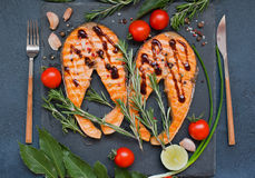 Top view of red fish salmon steak. S on dark stone background with herbs Royalty Free Stock Image