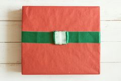 Top view red gift box with ribbon on white wooden plank background.  Stock Images