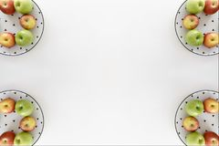 Top view of Red and green apples in white plate with black triangles pattern on four corners with white background Stock Image