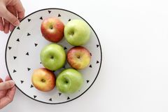 Top view of Red and green apples in white plate with black triangles pattern with hands on the left side with white background.  Royalty Free Stock Photo