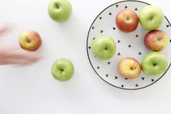 Top view of Red and green apples in white plate with black triangles pattern and apples with moving hand  on white background.  Stock Photos