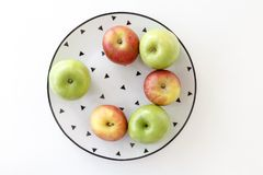 Top view of Red and green apples in white plate with black triangles pattern on white background Royalty Free Stock Image