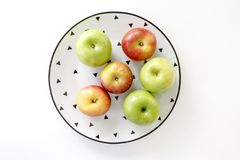 Top view of Red and green apples in white plate with black triangles pattern on white background Royalty Free Stock Photo
