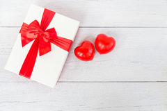 Top view red heart and gift box with ribbon on white wooden plan Royalty Free Stock Photos