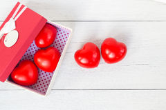 Top view red heart and gift box with ribbon on white wooden plan Stock Images