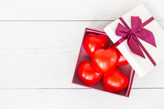 Top view red heart and gift box with ribbon on white wooden plan Royalty Free Stock Image