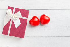 Top view red heart and gift box with ribbon on white wooden plan Stock Photography