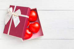 Top view red heart and gift box with ribbon on white wooden plan Stock Photos