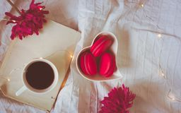 Top view of red or pink macarons in a heart shaped bowl, coffee, book and flowers royalty free stock photo