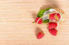 Top view of red ripe raspberries scattered from basket to wooden. Table, close up Royalty Free Stock Images