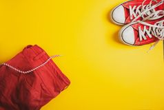 Top view of red sneakers and red shorts on yellow background stock images