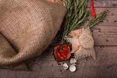 Top view of red spicy chili pepper in a glass jar, shucks of quail eggs and twigs of rosemary on a wooden background. Stock Image