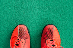 Top view of red sport shoes on green floor Royalty Free Stock Photos