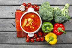 Top view of red tomato soup on wooden table. Fresh vegetables ar Royalty Free Stock Photo