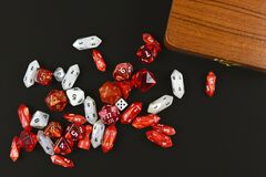 Top view of red and white role playing RPG dice of different shape on black background