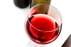 Top of view of red wine glass near wine bottles Stock Image