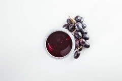 Red wine in grass and ripe grapes isolated on white. Top view of red wine in grass and ripe grapes isolated on white Royalty Free Stock Photo