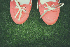 Top view of red worn woman shoes over grass textured background Royalty Free Stock Image