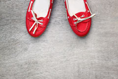Top view of red worn woman shoes over wooden textured background. instagram style filter Royalty Free Stock Image