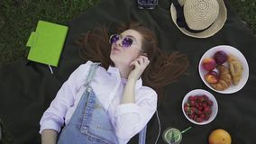 Ginger young girl in sunglasses and overalls lying on grass listening to music stock video