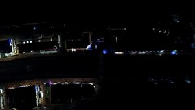 Top view of reflection of light from houses at night. Dim light from houses illuminates night streets of city and small. Canal with river stock video footage