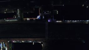 Top view of reflection of light from houses at night. Dim light from houses illuminates night streets of city and small. Canal with river stock video
